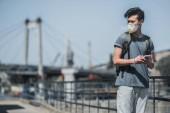 """Постер, картина, фотообои """"Азиатский подросток в противогаз Холдинг смартфон и глядя, концепция загрязнения воздуха"""""""