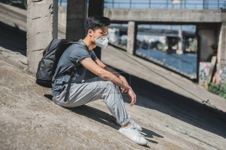 side view of asian teen in protective mask sitting under bridge, air pollution concept