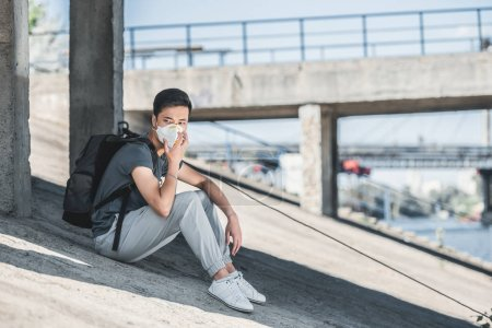 asian teen in protective mask sitting under bridge, air pollution concept