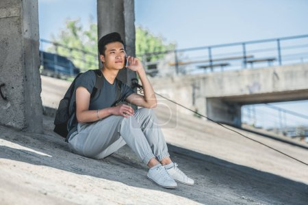asian teenager talking by smartphone while sitting under bridge in city