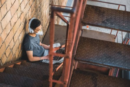 high angle view of asian teen in protective mask listening music with laptop on staircase, air pollution concept