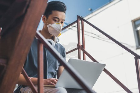 asian teen in protective mask using laptop on staircase, air pollution concept