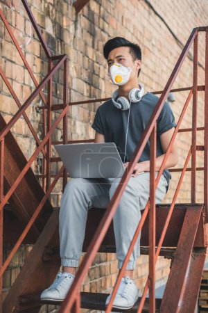 asian teen in protective mask sitting with laptop on staircase and looking away, air pollution concept