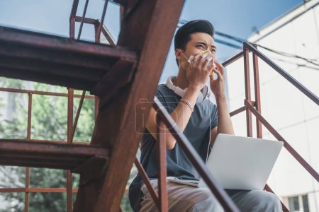 asian teen in protective mask sitting with laptop on staircase, air pollution concept