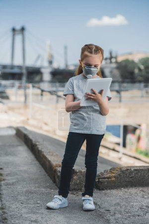child in protective mask using tablet on street, air pollution concept