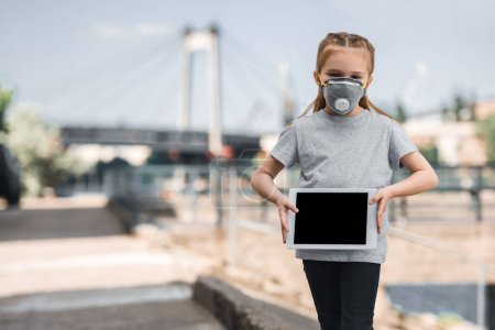 child in protective mask showing tablet on street, air pollution concept
