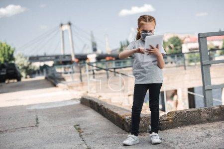 Photo pour Enfant en masque de protection utilisant comprimé, concept de pollution de l'air - image libre de droit