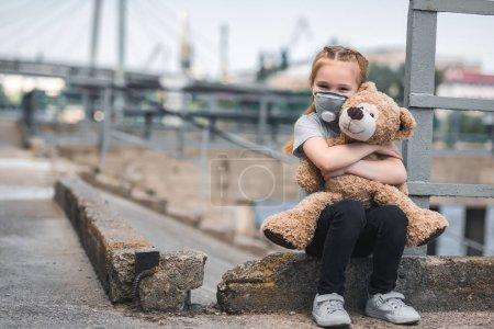 Photo pour Enfant dans un masque de protection étreignant ours en peluche dans la rue, concept de pollution atmosphérique - image libre de droit
