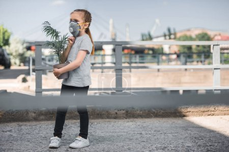 Photo for Child in protective mask carrying green potted plant, air pollution concept - Royalty Free Image