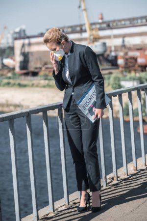 businesswoman touching protective mask on bridge, air pollution concept