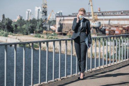 Photo pour Femme d'affaires en masque de protection parler par smartphone sur le pont, concept de pollution de l'air - image libre de droit
