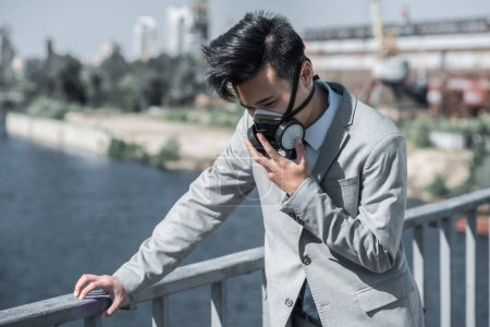businessman in protective mask having problem with breathing on bridge and leaning on railing, air pollution concept