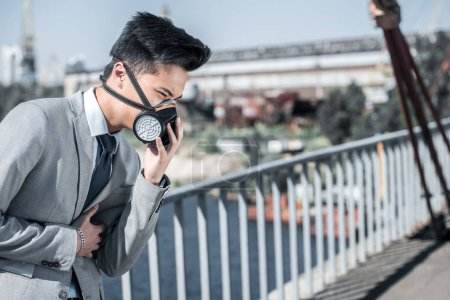 businessman in protective mask having problem with breathing on bridge, air pollution concept