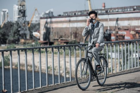 asian businessman in gas mask riding bicycle on bridge and talking by smartphone, air pollution concept