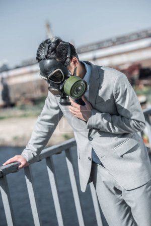 businessman in gas mask having problem with breathing on bridge and leaning on railing, air pollution concept