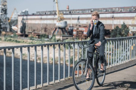 businesswoman in protective mask riding bicycle on bridge and talking by smartphone, air pollution concept