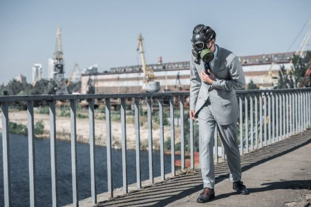 businessman in gas mask walking on bridge, air pollution concept