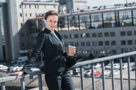 attractive businesswoman standing on bridge with disposable coffee cup