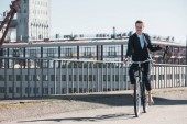 attractive businesswoman riding bicycle on bridge and holding shoes