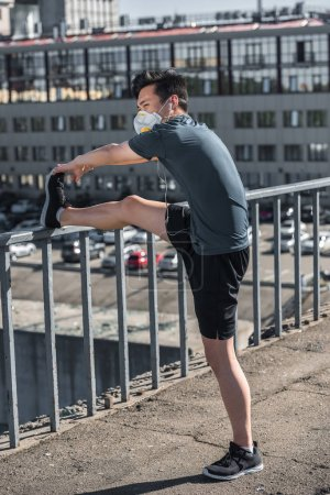 athletic asian teenager stretching legs in protective mask on bridge, air pollution concept