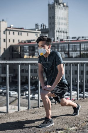 athletic asian teenager stretching in protective mask on bridge, air pollution concept