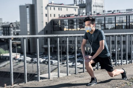 asian teen stretching legs in protective mask on bridge, air pollution concept