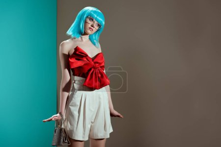 beautiful fashionable girl in blue wig posing and looking away in studio