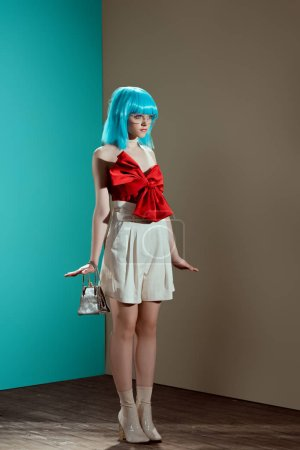 beautiful stylish young woman in blue wig pretending to be a doll and looking away