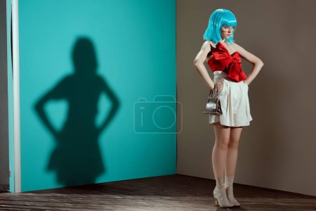 full length view of beautiful fashionable female model in blue wig posing with hands on waist and looking away