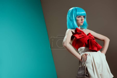low angle view of beautiful female model in blue wig standing with hands on waist and looking away