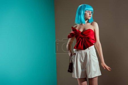 Photo pour Beau modèle féminin à la mode dans la perruque bleu posant et en regardant loin dans studio - image libre de droit