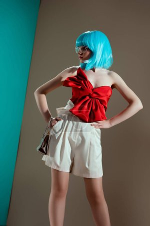 beautiful fashionable girl in blue wig and red bow standing with hands on waist and looking away in studio
