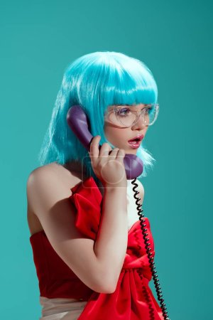 shocked stylish girl in blue wig talking by telephone and looking away isolated on blue