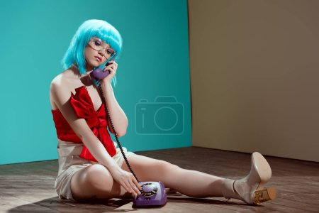 beautiful stylish girl in blue wig talking by handset while sitting on floor