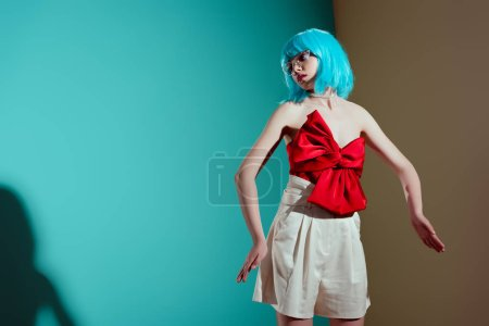 stylish girl in blue wig and red bow posing in studio