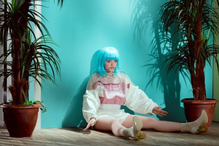 beautiful fashionable girl in blue wig pretending to be a doll and sitting on floor between potted plants