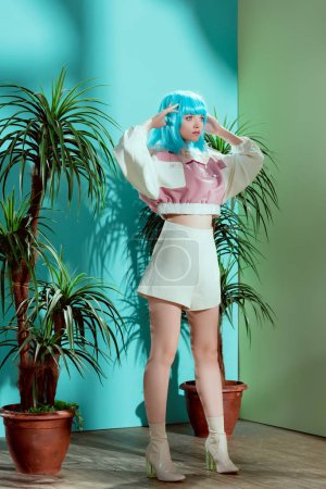full length view of stylish girl in blue wig pretending to be a doll and looking away