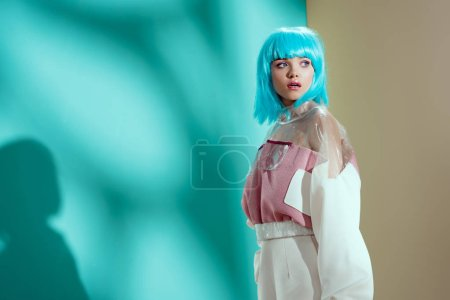 portrait of beautiful stylish young woman in blue wig looking away in studio