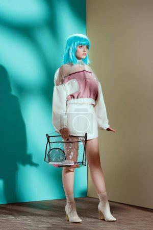 full length view of beautiful stylish girl in blue wig holding transparent cosmetic bag and looking away