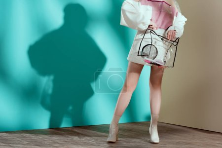 low section of fashionable young woman holding transparent cosmetic bag