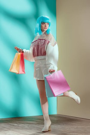 full length view of beautiful stylish young female model in blue wig holding shopping bags and looking away