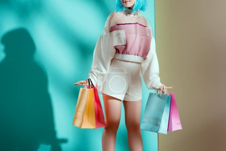 cropped shot of pretty stylish girl in blue wig holding shopping bags in studio
