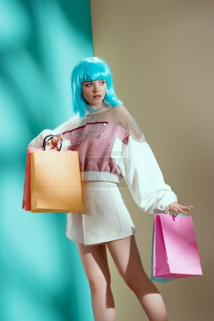 attractive stylish girl in blue wig holding paper bags and looking away in studio