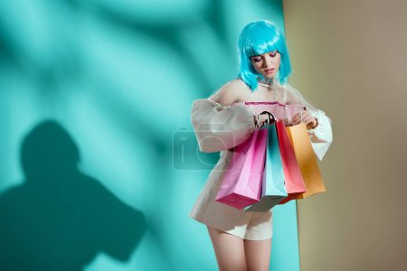 fashionable young female model in blue wig holding shopping bags in studio