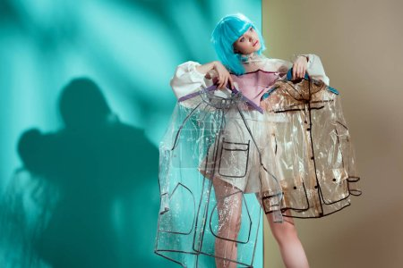 pretty stylish girl in blue wig holding hangers with transparent raincoats