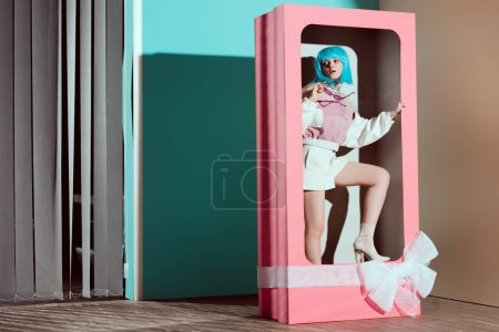 attractive stylish girl in blue wig posing in decorative pink box with bow
