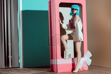 fashionable young woman in blue wig posing in decorative pink box with bow