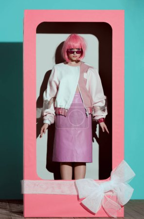 Foto de Hermosa chica de moda en peluca rosa en caja decorativa con arco y mirando a cámara - Imagen libre de derechos