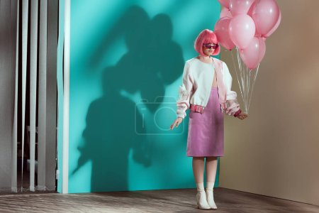 full length view of stylish pretty girl in bright wig holding pink balloons
