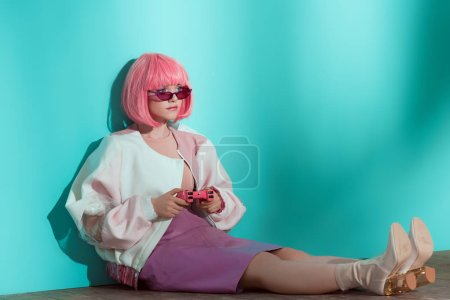 Photo for Fashionable pretty girl in pink wig sitting on floor and using joystick - Royalty Free Image